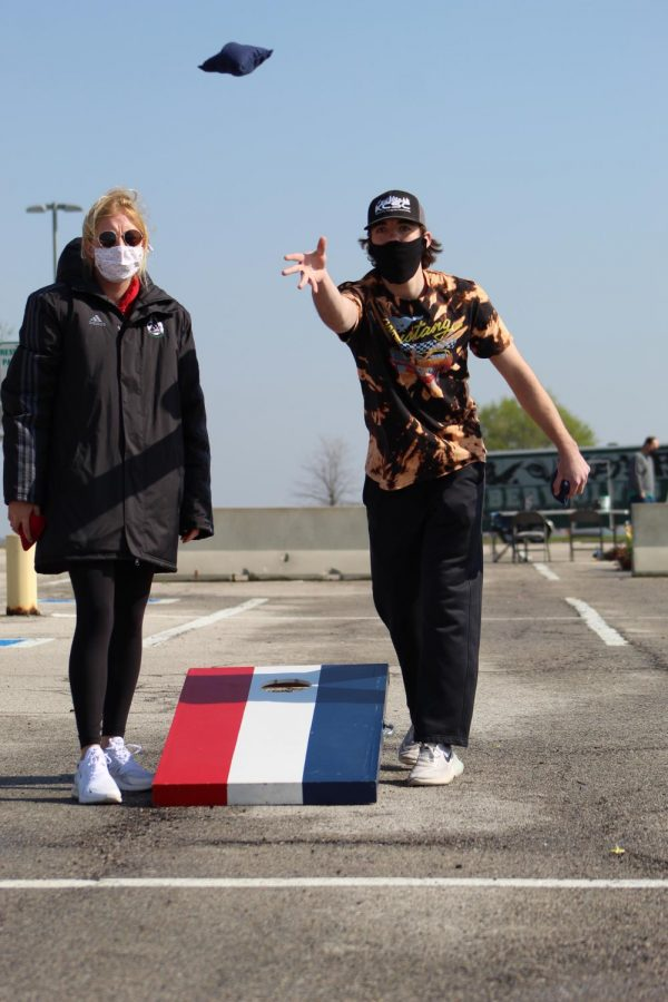 With an outstretched arm, senior Keithan Sharp tosses one of his cornhole bags at Cornhole for a Cure on April 24, 2021. Sharp played with senior Lauren Weber as his partner.