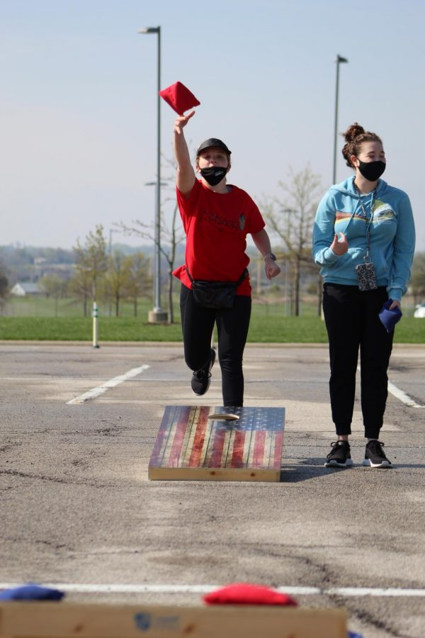 Foot in the air, senior Olivia Parsons lets go of her cornhole bag at Cornhole for a Cure on April 24, 2021. Parsons and her partner senior Anna Comstock made custom shirts for their team.