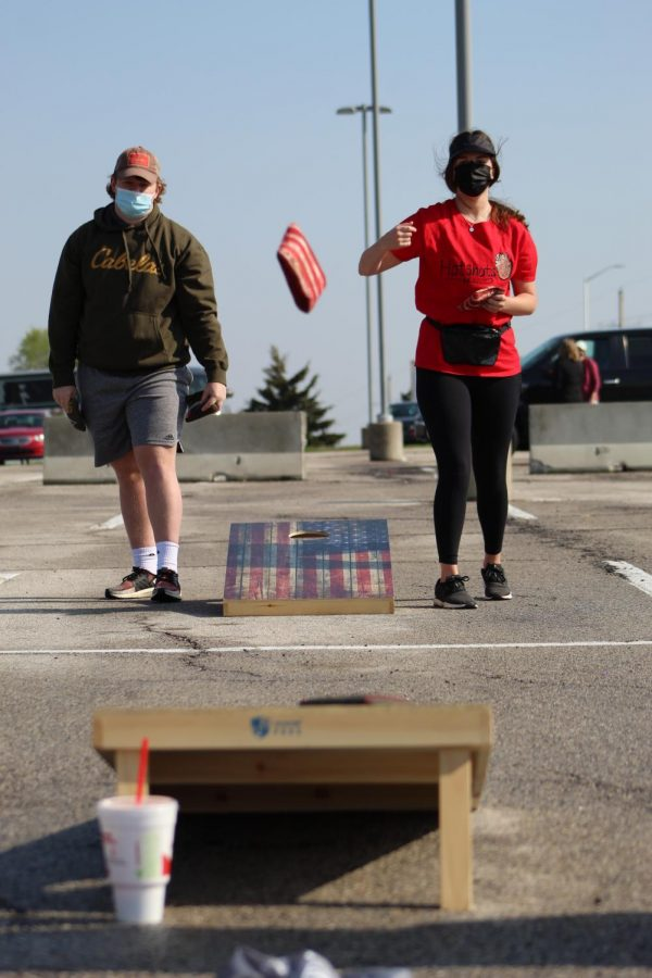 Watching her cornhole bag fly, senior Anna Comstock competes in Cornhole for a Cure on April 24, 2021. Cornhole for a Cure consisted of two sessions where the winners of each session competed against each other at the end.
