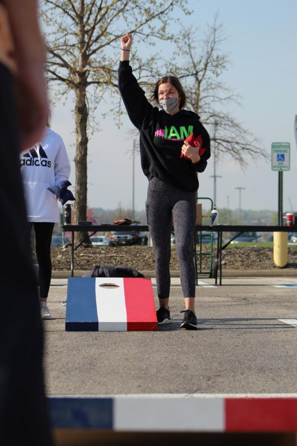 Hand in the air, senior Alex Ogren celebrates her successful throw at Cornhole for a Cure on April 24, 2021. Ogren participated in Cornhole for a Cure as a competitor as well as a member of Wolf Pack Crew and Student Council.