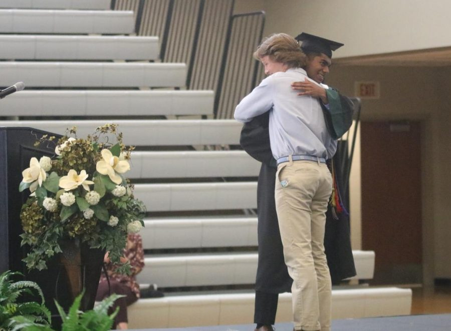 Handing off the keys to the class, senior Karthik Sathish and junior Josh Peterson bro hug on stage at class day on May 21.