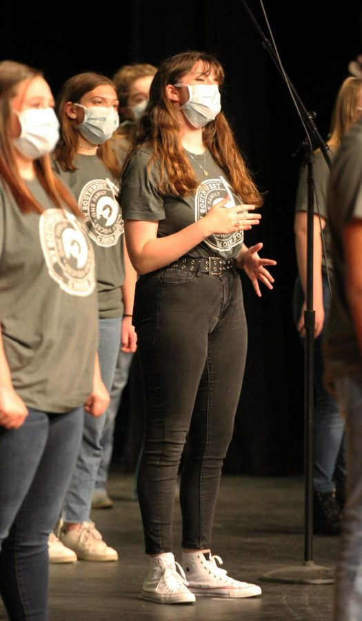 With her hands up, junior Carolyn Brotherson sings passionately on stage.