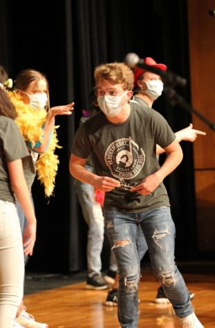 Sunglasses in hand, junior Sam Illum looks to his peers as he performs on stage.