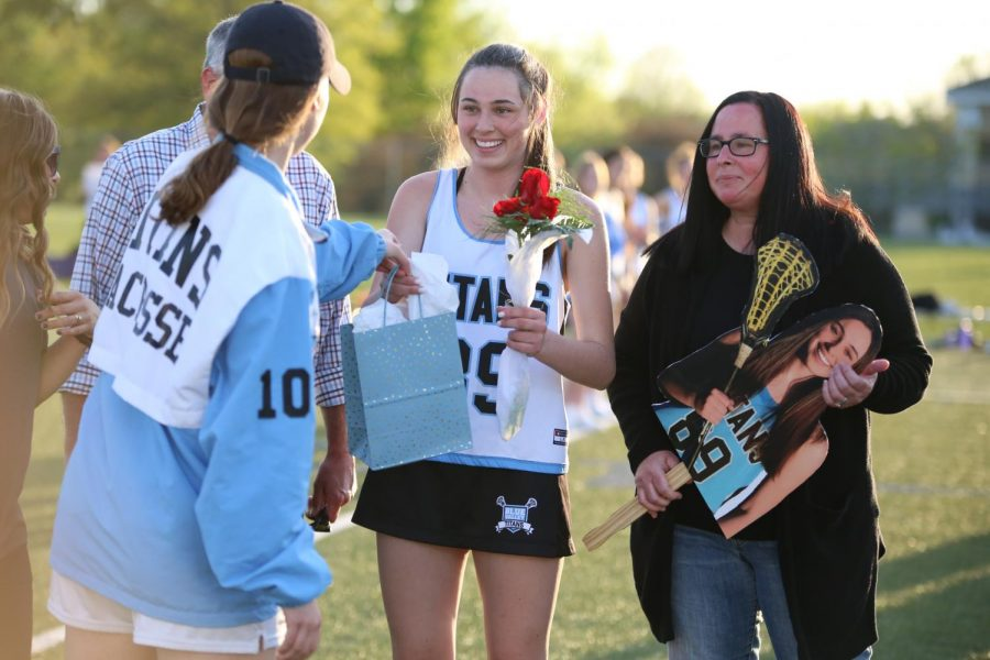 Being handed her gift, senior Avery Kotel gathers her items before posing for a photo with her parents and coaches on April 29.