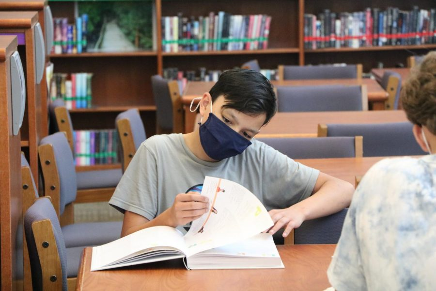Looking through the pages, freshman Sean Quijano looks through this year's yearbook on Distribution Day on May 19.