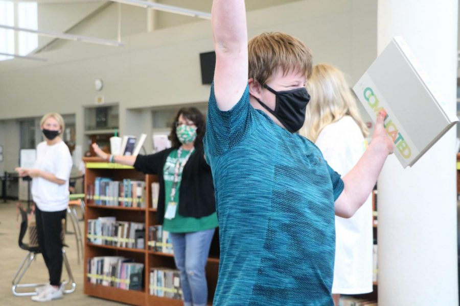 Hand in air, junior Kessler Sweat receives his book on Distribution Day on May 19.