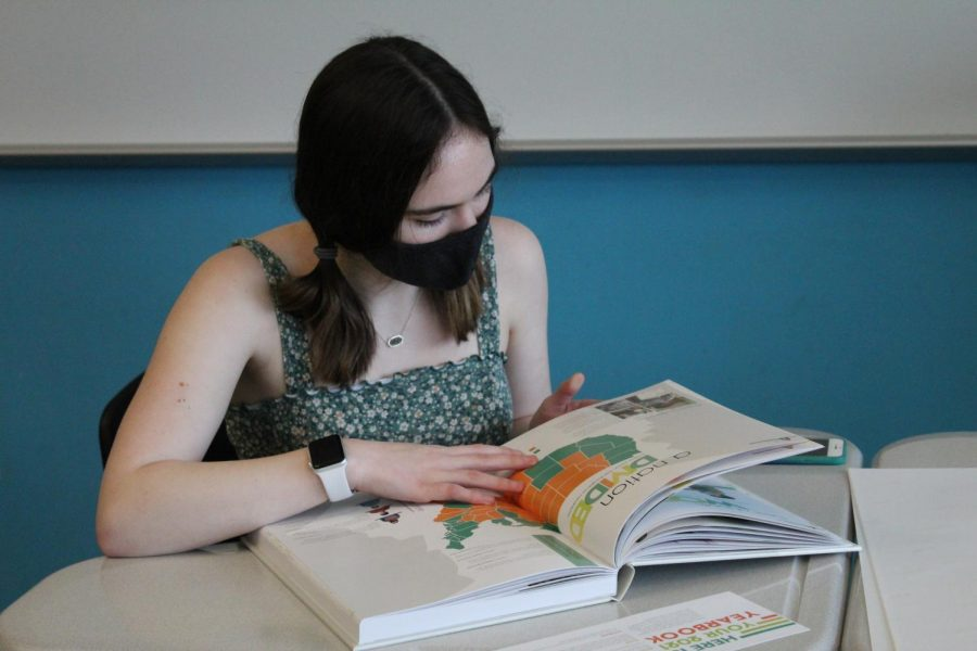 Natalie Robben flips the page as she goes through the yearbook.