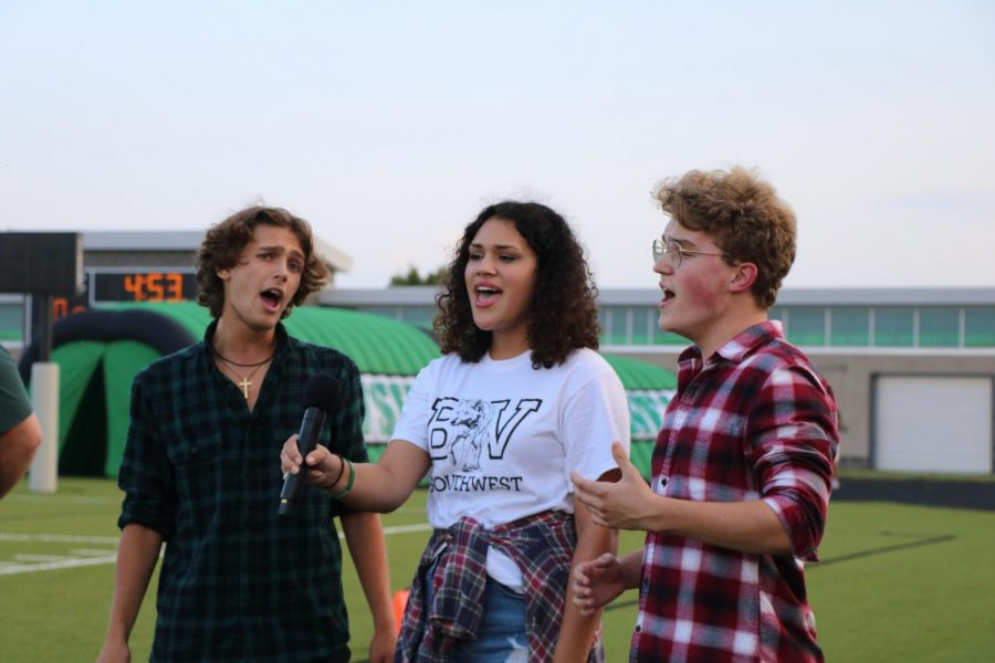 Seniors Jonah West, Kennadie Campbell and Sam Illum sing the National Anthem prior to the start of the game.
