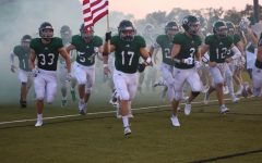 Senior Davis Brogan carries the flag out of the pregame tunnel at the Senior night football game on Sept.3.